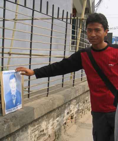 A boy tired to pic up a placard, with photo of Umesh Chandra Thapa who was killed in Dang by army on the election day