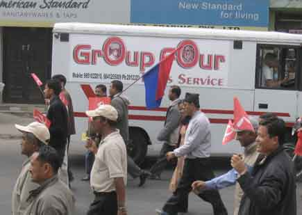 A rally passes by a Group Four van in Tripureshwor