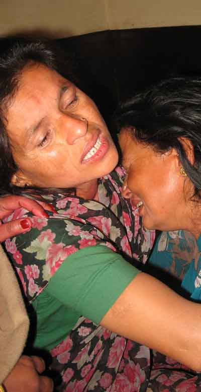 Sushila Sharma, right, is being consoled by her sister. Sushila lost consciousness hearing the news the death of her husband, 50-year-old Sahadev Sharma, in an indiscriminate Wednesday firing by police upon a crowd that was peacefully celebrating Holi