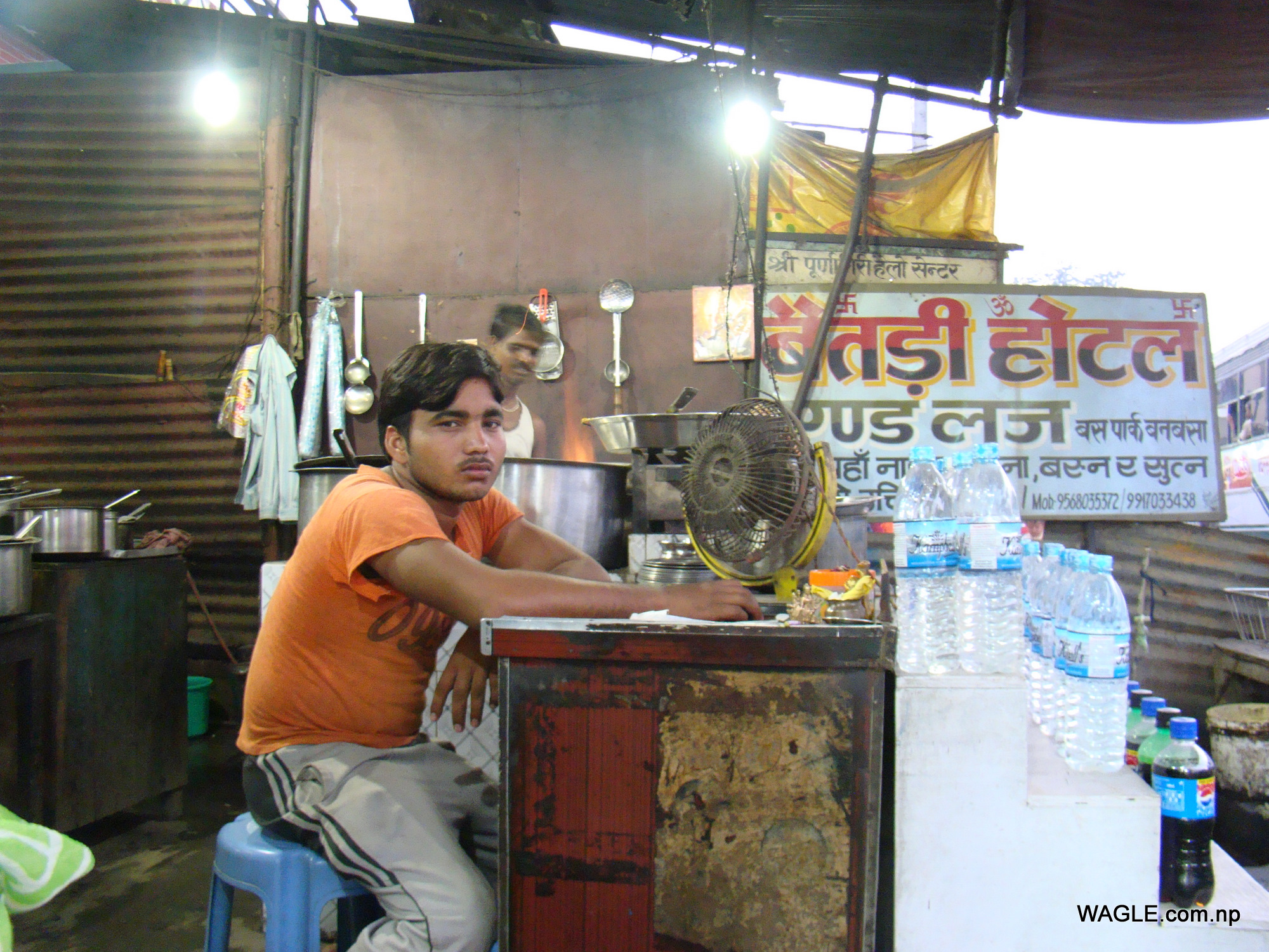An Indian man waits for customers at the counter of his eatery- Baitadi Hotel- in Banbasa, India that is named after a district of Nepal in far west that borders India. The sign board assures good food in Nepali language. Banbasa, a border town, is the starting point for many buses that reach Delhi in about 9 hours.