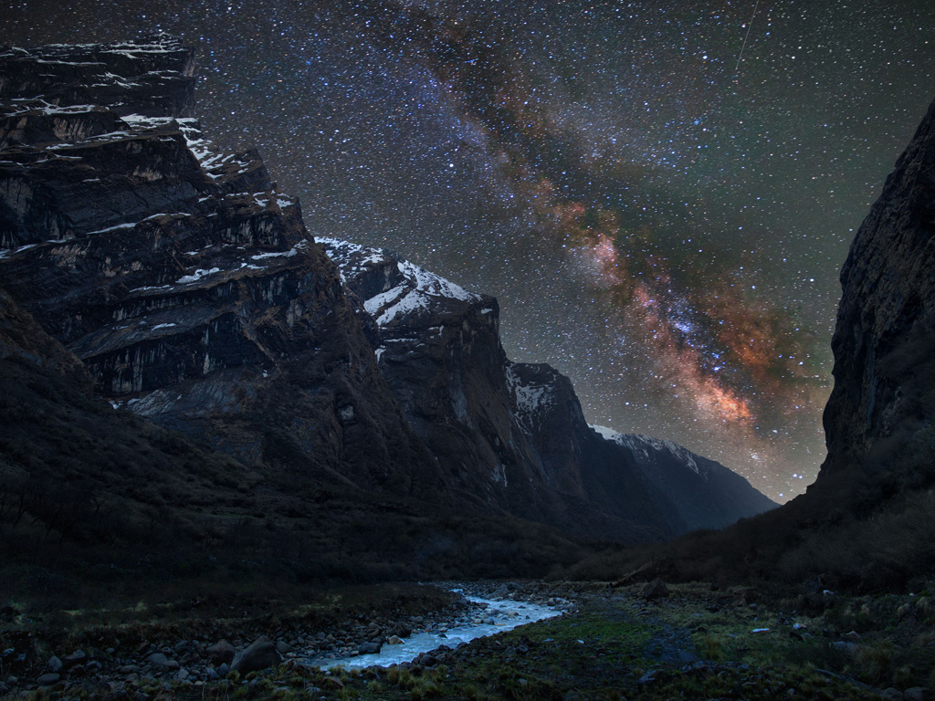 The Milky Way as seen in the Mardi Khola valley in the Himalayas, with clouds of galactic dust illuminated in red by young stars. Anton Jankovoy braved freezing temperatures for this shot during a trek in Nepal Photograph: Anton Jankovoy/ Caters News Agency