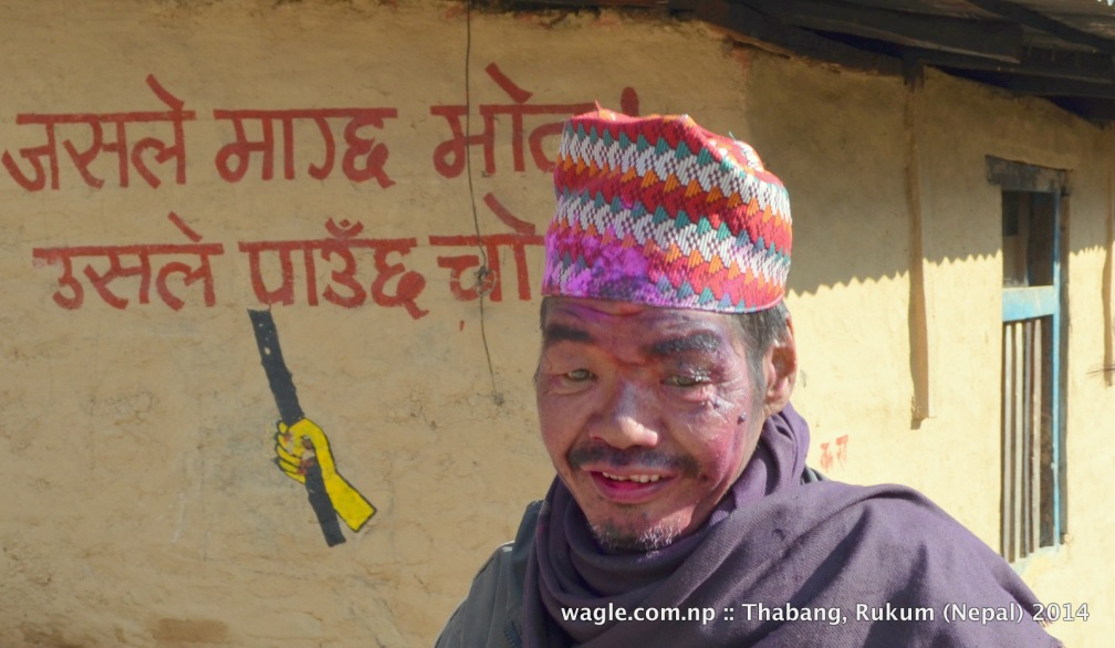 "A man in Thabang, Rolpa, face smeared with colored powder, celebrated Maghi festival. On the background is an anti-election slogan- ""the one who asks for vote will get chot (hurt)."""